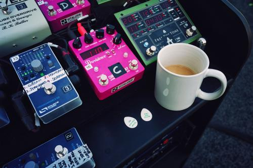 A pair of programmable MIDI EQ pedals, Vitalizer digital delay pedal, Free The Tone digital delay, picks, and all-important cup of tea.